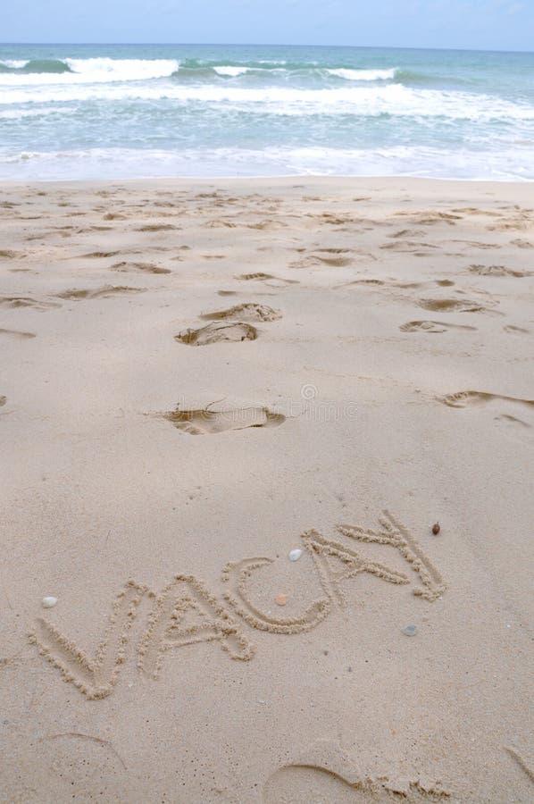 Sformułowania Vacay na Plażowym piasku z morze fala zdjęcie stock