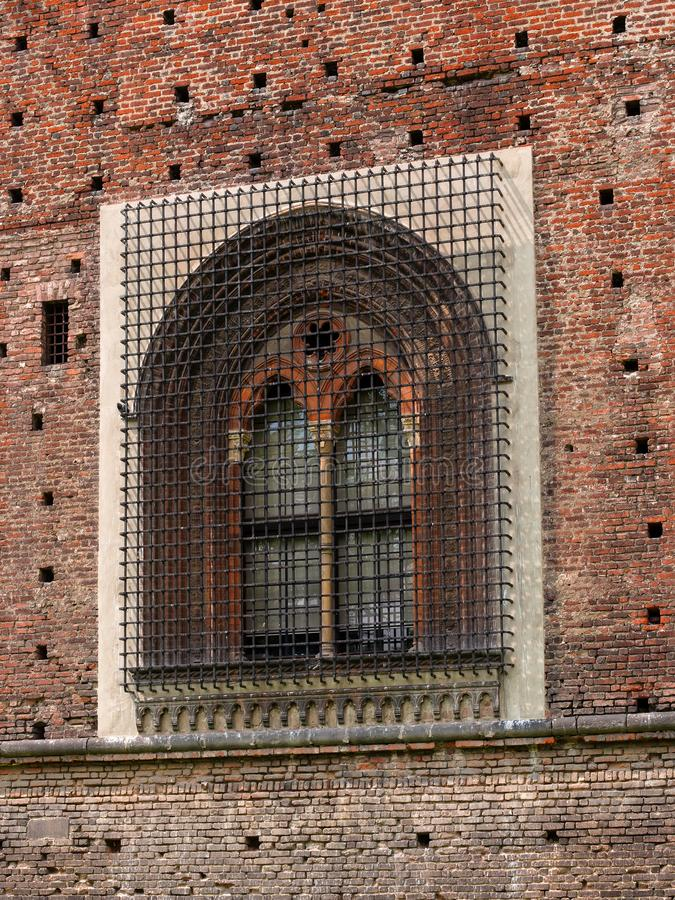 Sforza Castle in Milan, northern Italy. Window on the fortress wall. On the window is a steel lattice royalty free stock photography