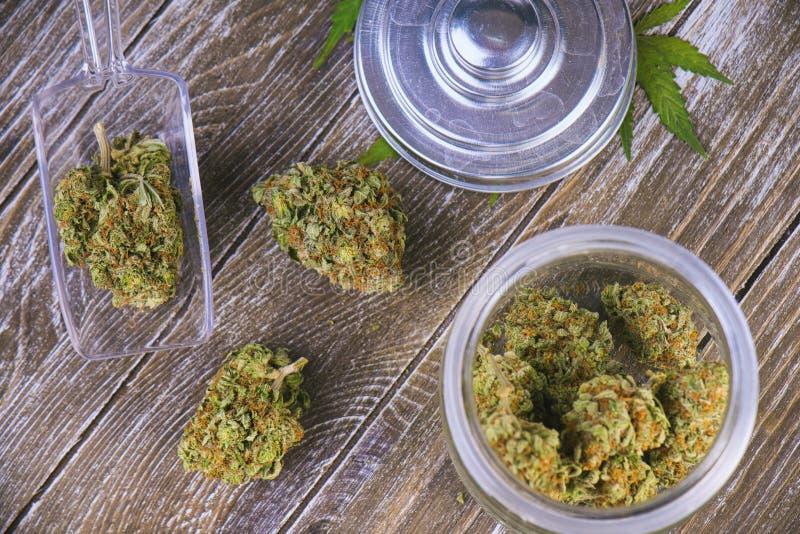 Sforzo del padrone dell'esploratore dei germogli della cannabis sul barattolo di vetro sopra backg di legno fotografie stock