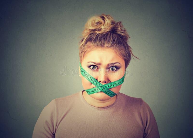 Sforzo di restrizione di dieta Donna frustrata con nastro adesivo di misurazione intorno alla sua bocca fotografie stock libere da diritti