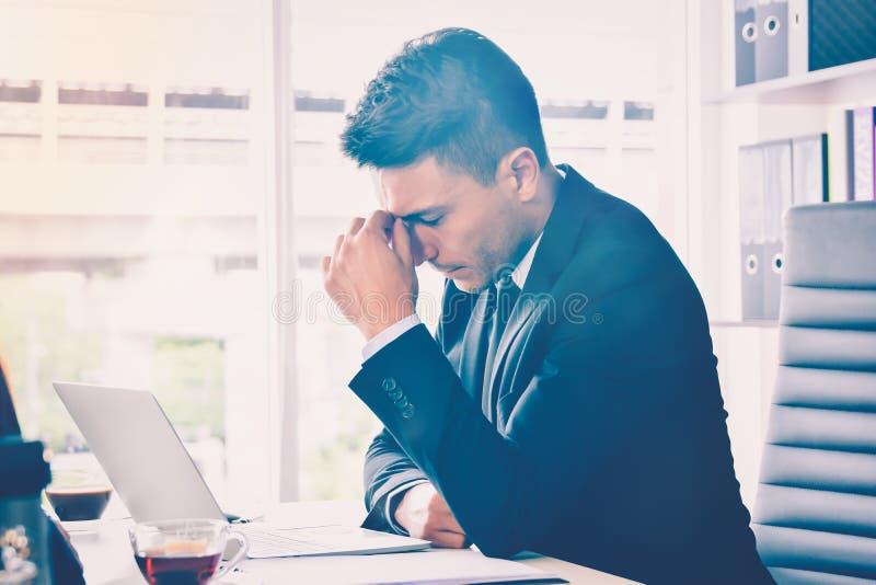 Sforzo o tensione dell'uomo di affari in ufficio con la sindrome di burnout allo sforzo ed al burnout relativi del lavoro di scri fotografie stock libere da diritti