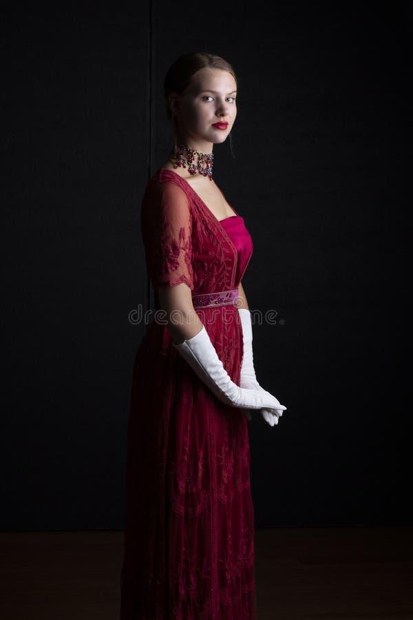 1910'sfrau im roten Spitzekleid und in der Kristallhalskette stockbilder