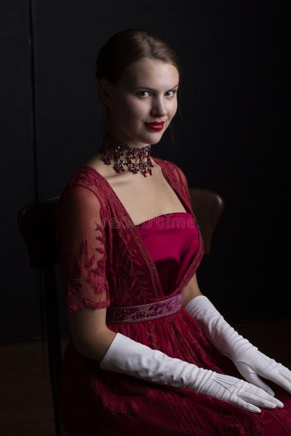 1910'sfrau im roten Spitzekleid und in der Kristallhalskette stockfotografie