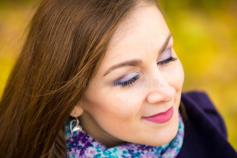 Sfreghi la bella ragazza con gli occhi chiusi su un fondo vago delle foglie di autunno fotografie stock libere da diritti
