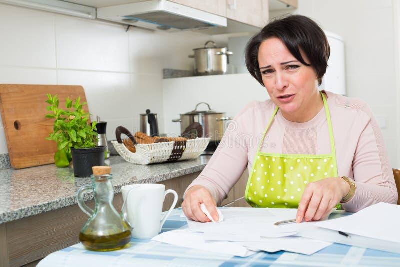 Sfrustowana kobieta z bankowość dokumentami indoors zdjęcia royalty free