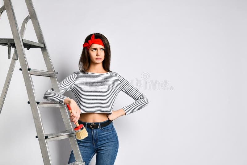 Sfrustowana Młoda brunetki dziewczyna z muśnięciem i stepladder - ile pracy mu robić na malować ściany fotografia stock