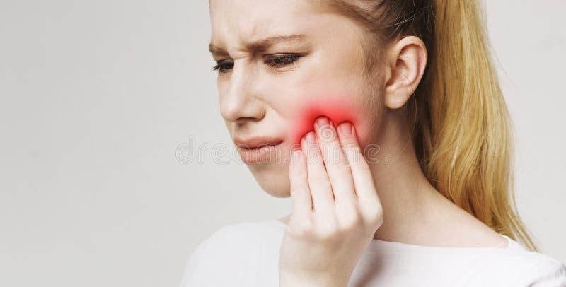 Sfrustowana młoda kobieta dotyka jej policzek z toothache zdjęcie royalty free