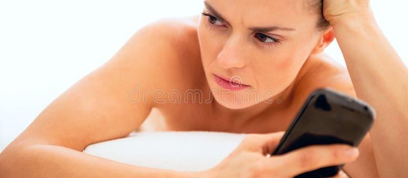 Sfrustowana młoda kobieta kłaść na masażu stole z telefonem komórkowym fotografia stock