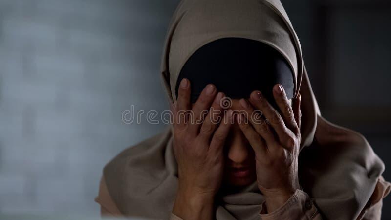 Sfrustowana muzułmańska dama w hijab nakrycia twarzy z rękami, życie problemy, stres zdjęcia stock