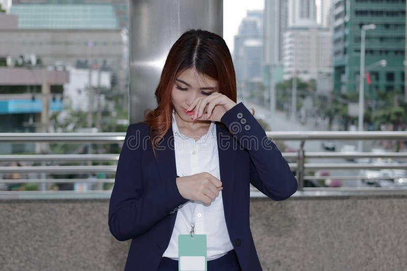 Sfrustowana przygnębiona młoda Azjatycka biznesowa kobieta w formalnym jednolitym płaczu przy miastowym miasta tłem fotografia royalty free