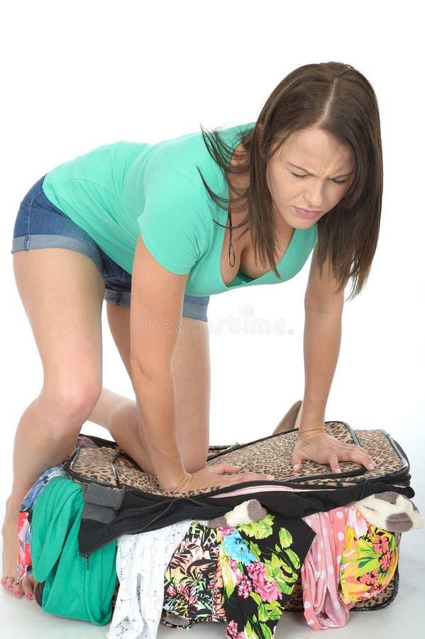 Sfrustowana Zaakcentowana młoda kobieta Próbuje Zamykać Przelewa się walizkę Patrzeje Karmiący Up zdjęcia stock