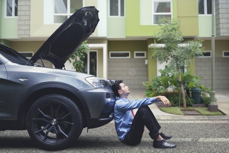 Sfrustowany biznesmen czuje beznadziejny opierać na jego awaria samochodzie obraz stock