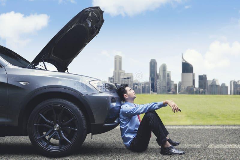Sfrustowany biznesmen opiera na łamanym puszka samochodzie zdjęcia royalty free