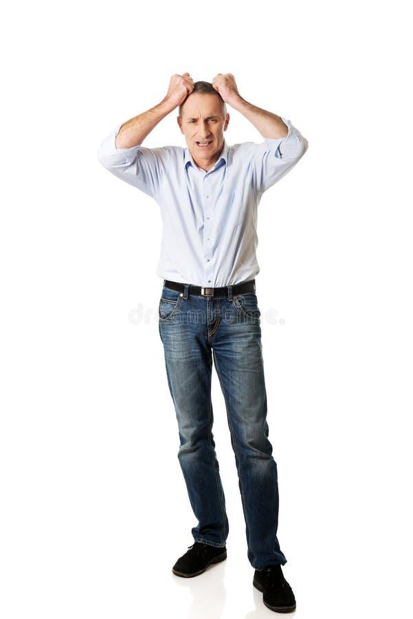 Sfrustowany mężczyzna ciągnie jego włosy fotografia stock