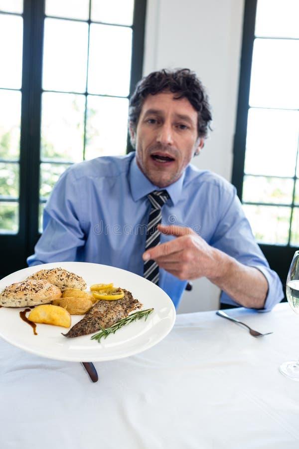 Sfrustowany mężczyzna trzyma talerza posiłek w restauraci obraz royalty free