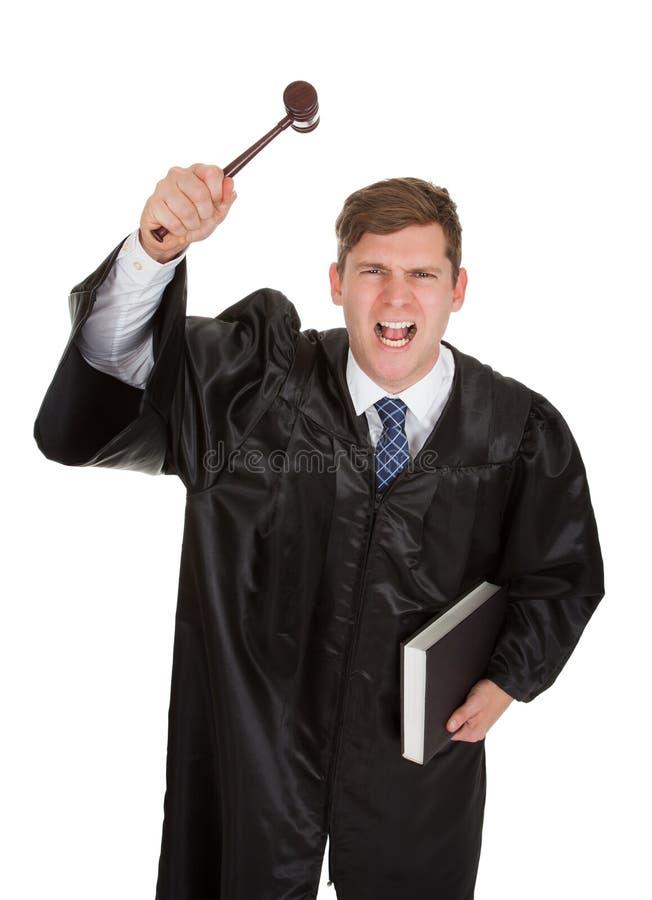Sfrustowany męski sędzia z młoteczkiem i książką obraz stock