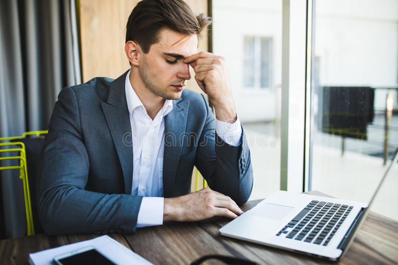 Sfrustowany młody biznesowy mężczyzna pracuje na laptopie przy biurem obrazy royalty free