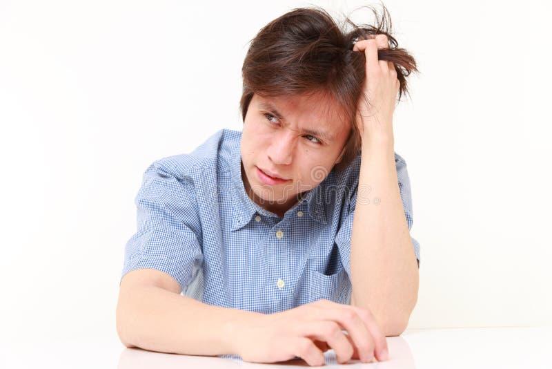 Sfrustowany młody człowiek ciągnie jego włosy zdjęcie stock