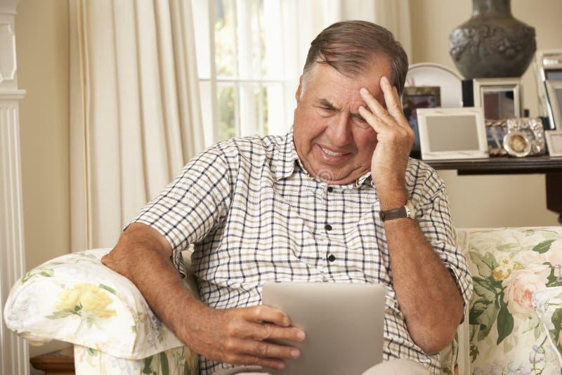 Sfrustowany Przechodzić na emeryturę Starszego mężczyzna obsiadanie Na kanapie Używa Cyfrowej pastylkę W Domu zdjęcie royalty free