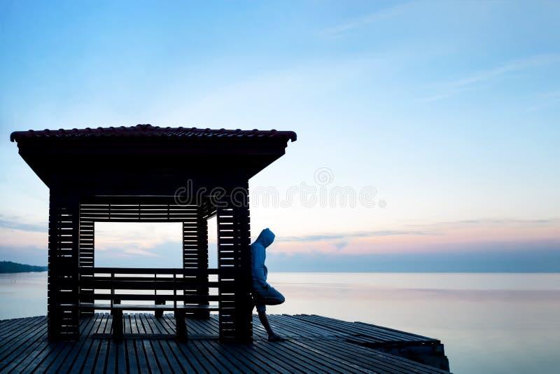 Sfrustowany przygnębiony mężczyzna jest ubranym hoodie stoi samotnie na drewnianym fotografia royalty free