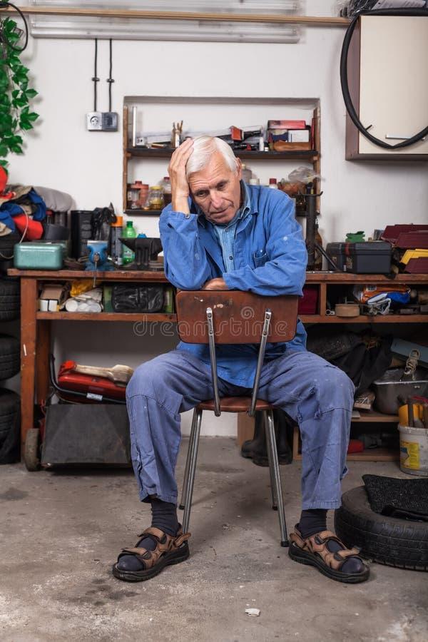 Sfrustowany starszy pracownik w warsztacie obraz stock