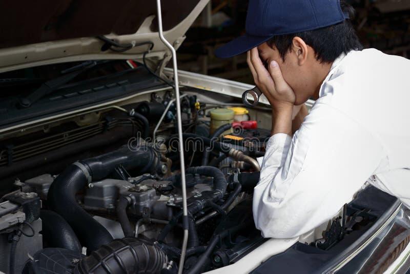 Sfrustowany zaakcentowany młody Azjatycki mechanika mężczyzna w bielu munduru nakrycia twarzy z rękami przeciw samochodowi w otwa fotografia royalty free