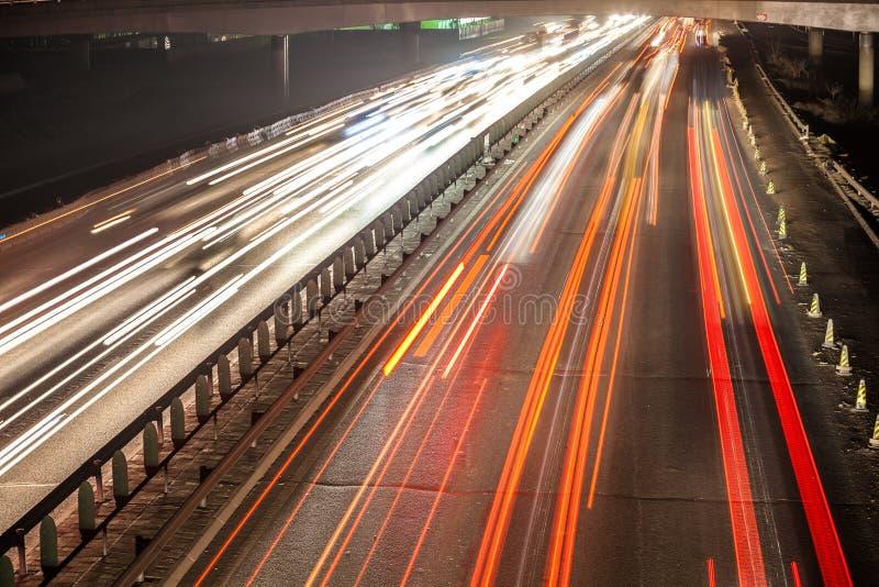 Sfuocatura di movimento occupata di traffico di notte immagine stock