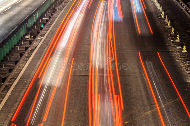Sfuocatura di movimento occupata di traffico di notte fotografie stock