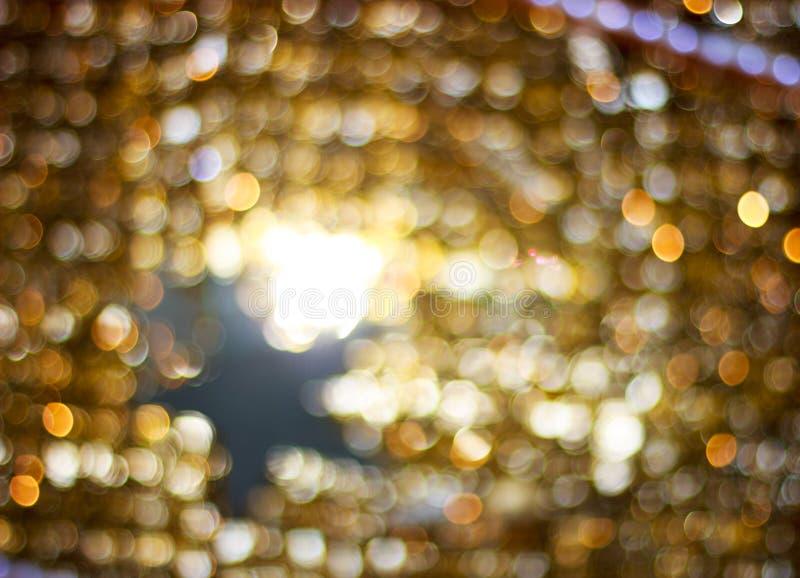 Sfuocatura dorata di Bokeh Luci brillanti dell'oro scuro Cerchi di Bokeh royalty illustrazione gratis