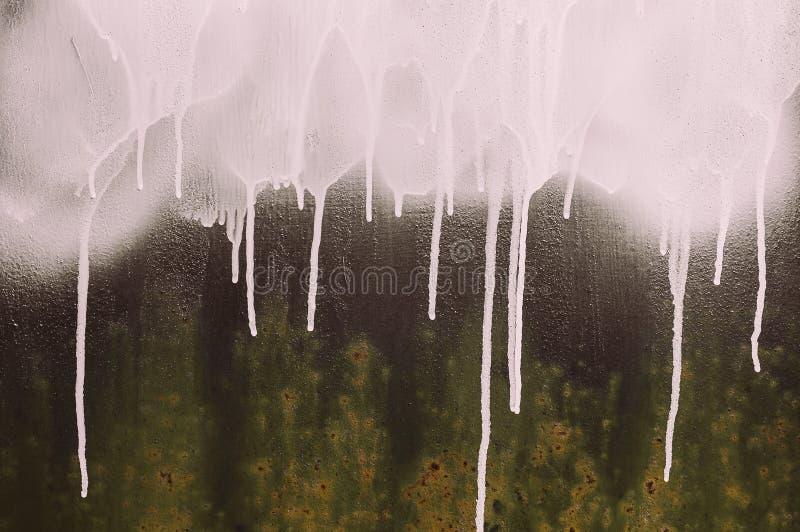 Sgocciolatura bianca della pittura di spruzzo immagini stock