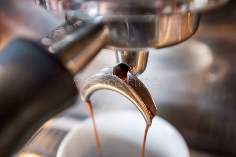 Sgocciolatura del caffè espresso dal portafilter della macchina del caffè in bianco fotografia stock libera da diritti