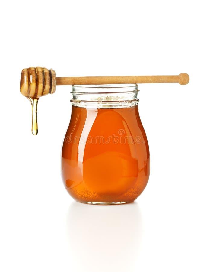 Sgocciolatura del miele dal drizzler in cima al vaso fotografie stock