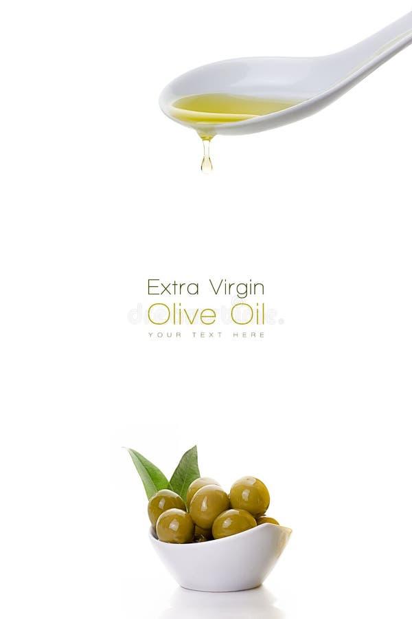 Sgocciolatura vergine dell'olio d'oliva da un cucchiaio e dai semi dell'oliva immagine stock