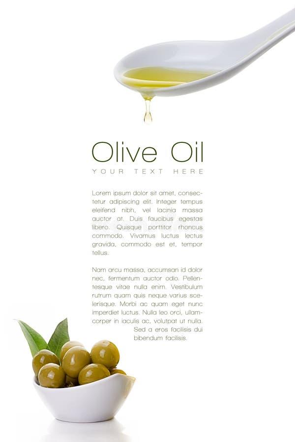 Sgocciolatura vergine dell'olio d'oliva da un cucchiaio e dai semi dell'oliva fotografia stock