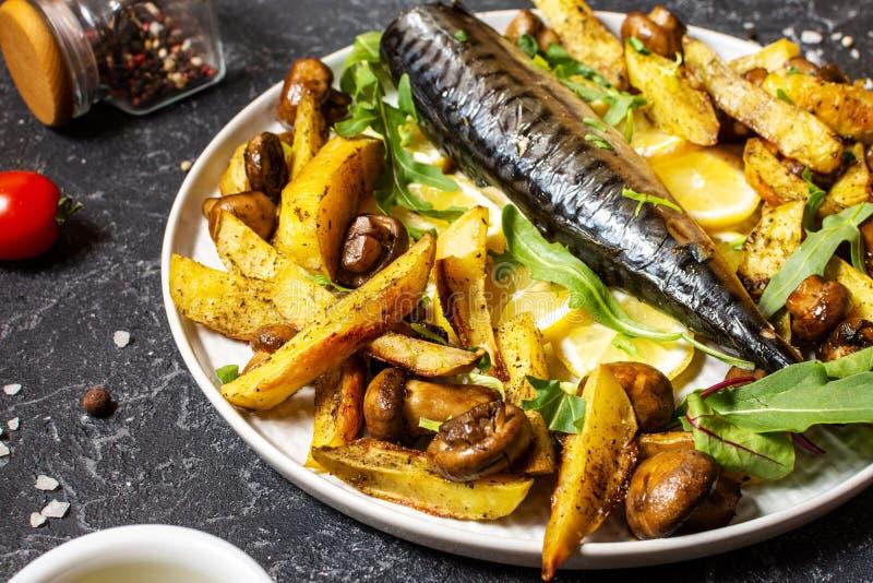 Sgombro cotto con limone, patate cotte e funghi su un piatto su fondo nero di pietra immagini stock