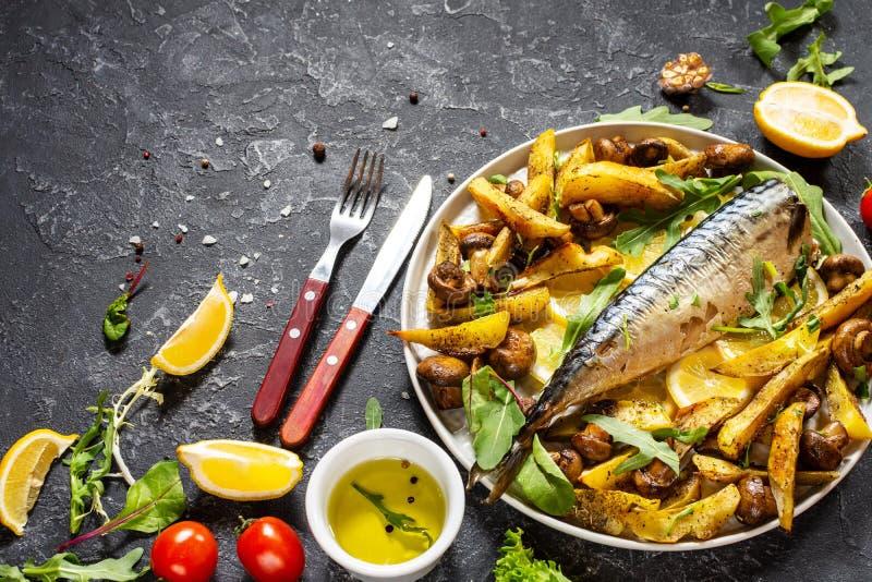 Sgombro cotto con limone, patate cotte e funghi su un piatto su fondo nero di pietra immagine stock libera da diritti