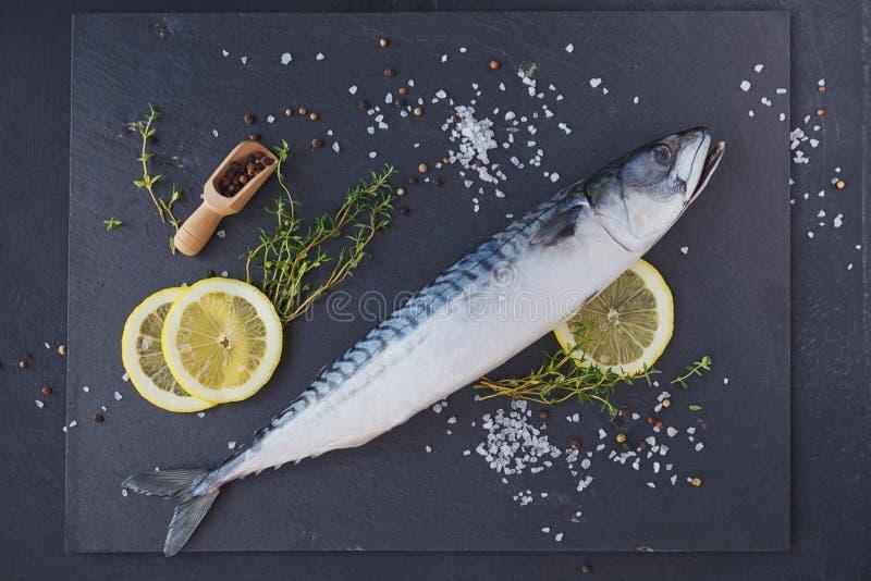 Sgombro fresco ed ingredienti del pesce crudo per la cottura sull'delle sedere scure fotografie stock libere da diritti