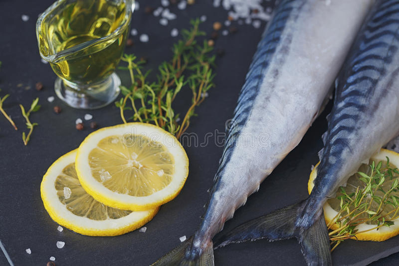 Sgombro fresco ed ingredienti del pesce crudo per la cottura sull'delle sedere scure fotografia stock libera da diritti