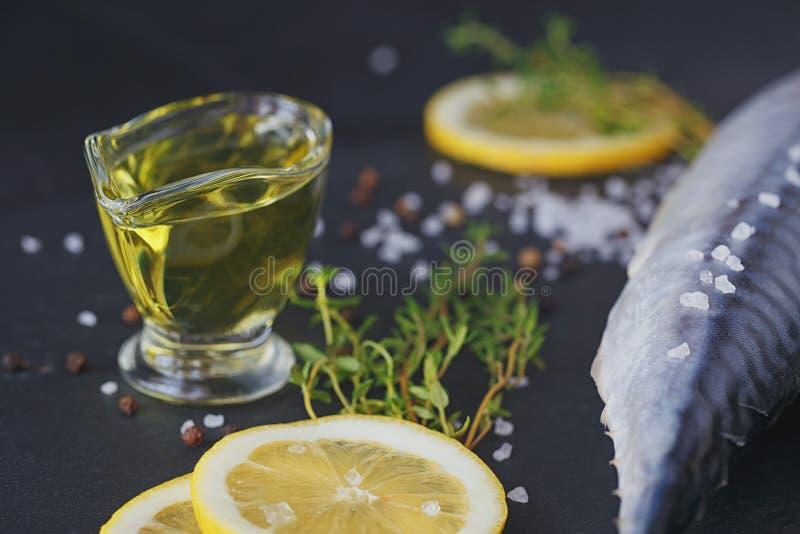 Sgombro fresco ed ingredienti del pesce crudo per la cottura sull'delle sedere scure immagine stock libera da diritti