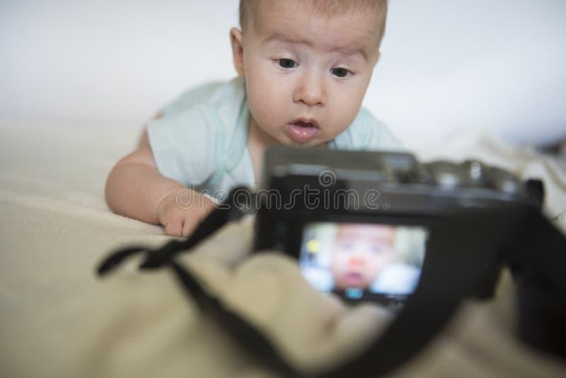 Sguardi domandantesi della piccola bella neonata al photocamera digitale immagini stock libere da diritti