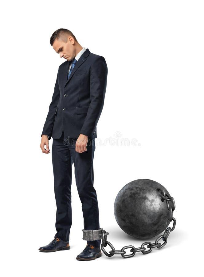 Sguardi tristi di un uomo d'affari giù mentre ostacolato ad una grande palla del ferro con una catena alla sua caviglia fotografia stock