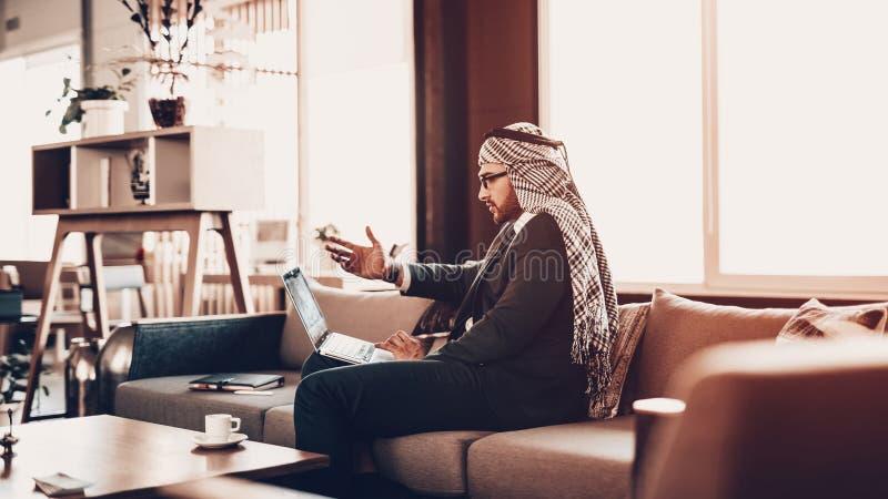 Sguardo arabo in computer portatile ed ondeggiando la sua mano immagini stock libere da diritti