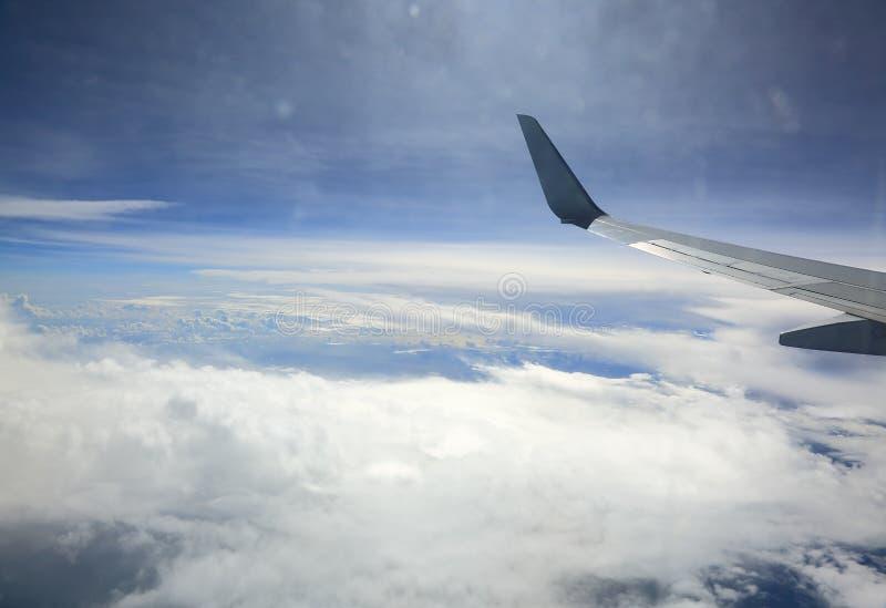 Sguardo dell'ala di aereo dalla finestra di cabina Cielo blu, nuvole bianche e terra dentro sotto fotografia stock libera da diritti