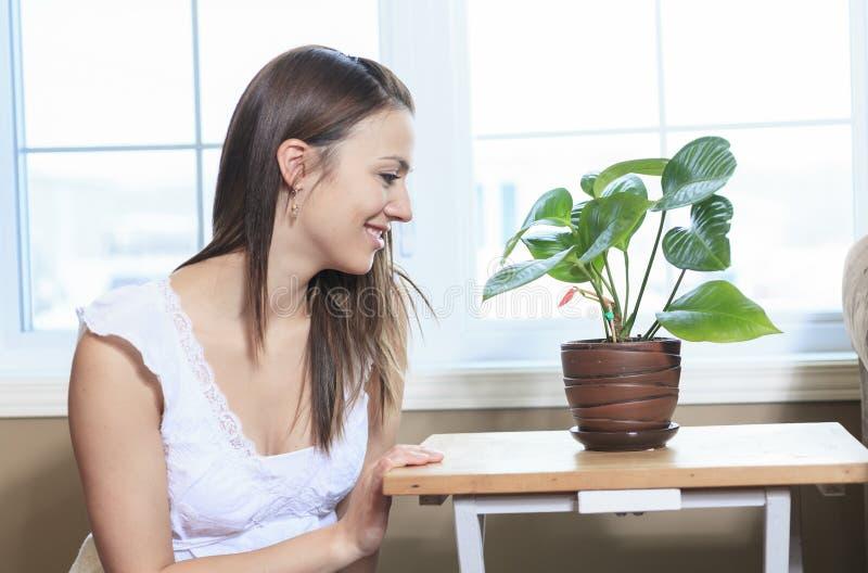 Sguardo della donna nelle piante nel salone immagini stock