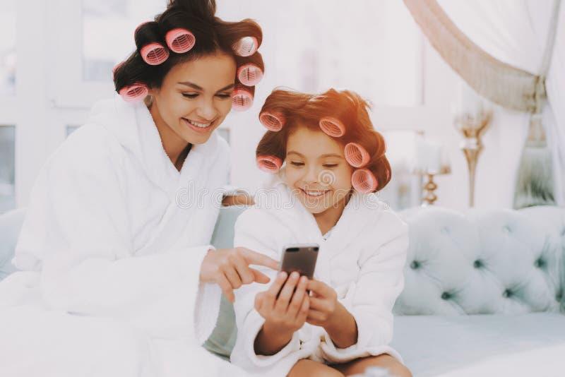 Sguardo della figlia e della mamma al telefono sul sofà blu in stazione termale immagini stock