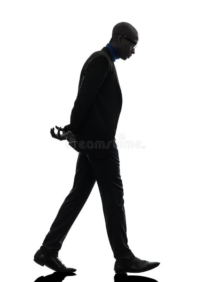 Sguardo di camminata dell'uomo di colore africano giù la siluetta fotografia stock