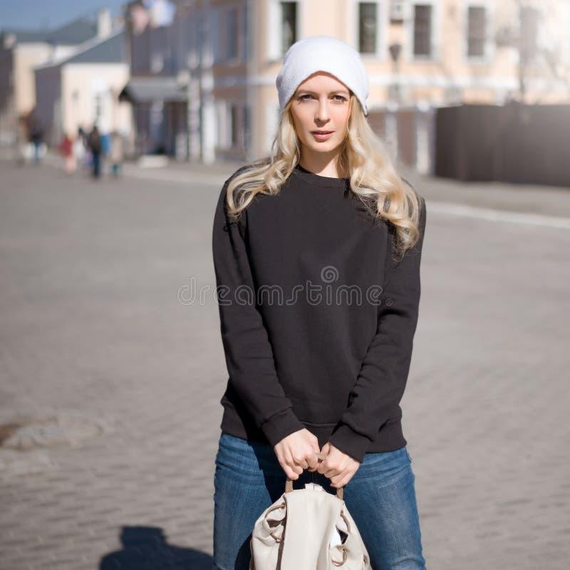 Sguardo di modo della via Bella ragazza in maglia con cappuccio nera fotografia stock libera da diritti