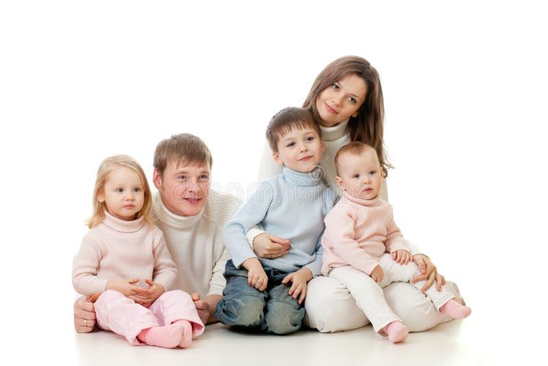 Sguardo di seduta della famiglia felice obliquamente fotografie stock libere da diritti