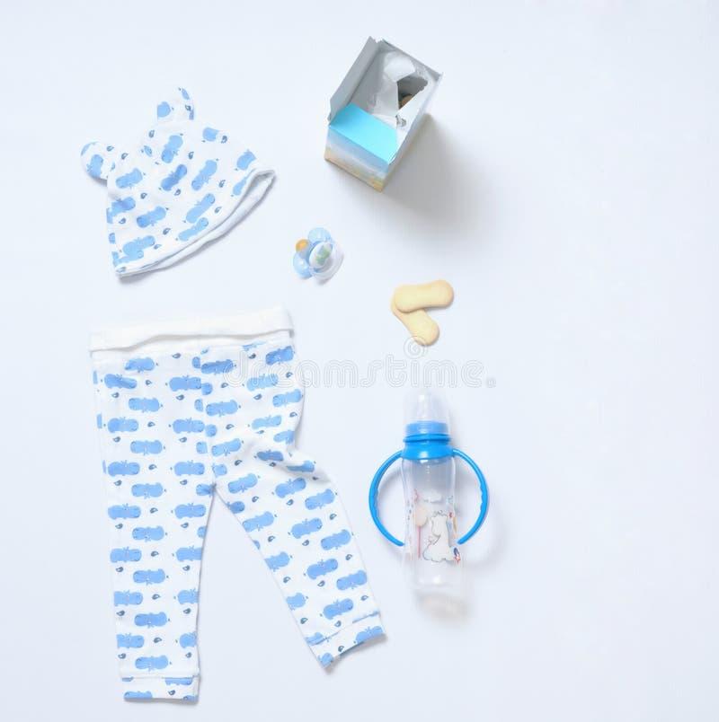 Sguardo di vista superiore dei vestiti del bambino e della roba del giocattolo fotografia stock