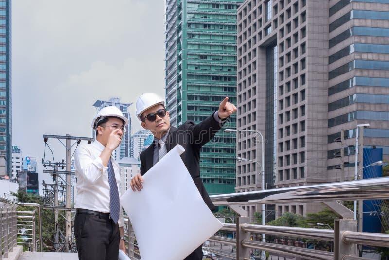 Sguardo e punto asiatici dell'uomo d'affari al dito via ed all'ingegnere fotografie stock